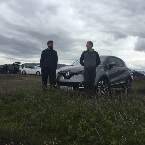 two men and a car in a field